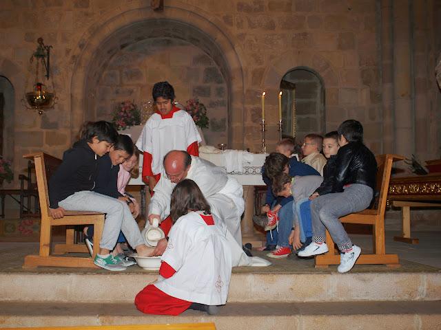 El párroco lava los pies a un conjunto de niños que representan a los apóstoles
