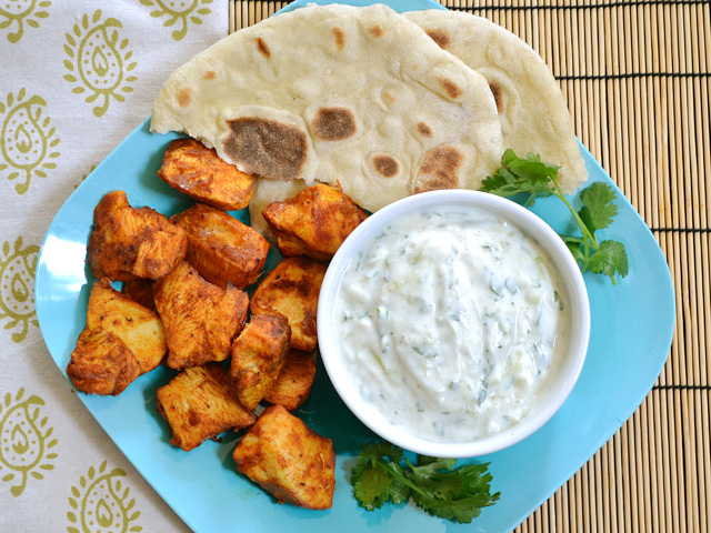 Plate of chicken bits and naan with a bowl of cucumber raita