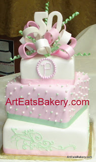 Three tier square pink, white and green fondant custom 50th birthday cake with monogram, pearls and bow