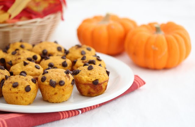 photo of a plate of Pumpkin Pancake Muffins with small pumpkins in the background