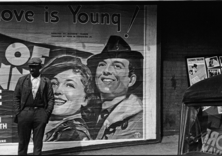 Man on Sidewalk in Front of Movie Poster