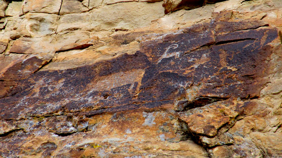 On each side of this petroglyph panel, there appear to be human figures pointing arrows at each other