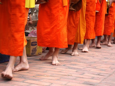 Feet of monks on their daily procession in Luang Prabang Laos
