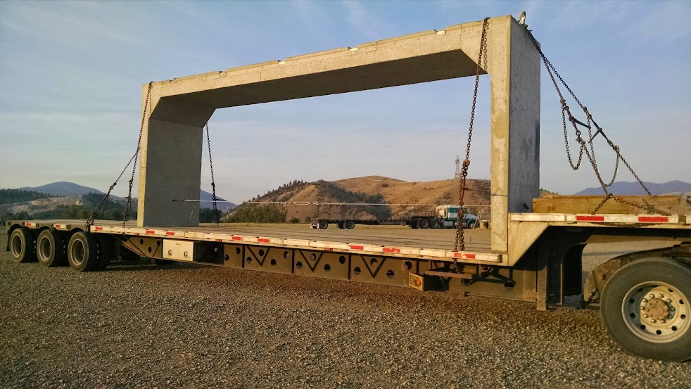 flatbed loaded with large cement bridge piece