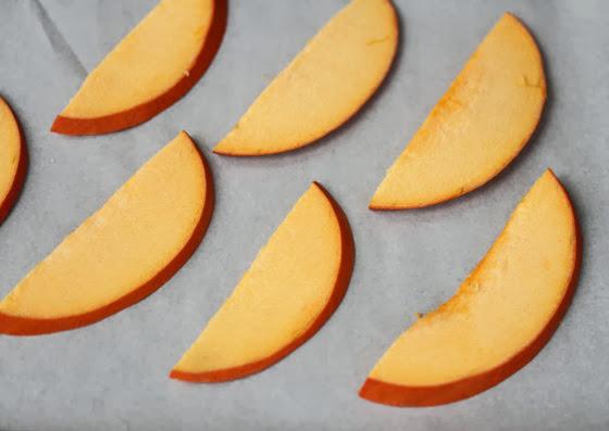 raw pumpkin slices on a baking sheet