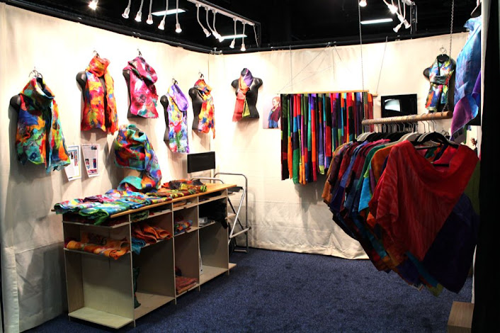 an artist's booth with scarves and other wearable art