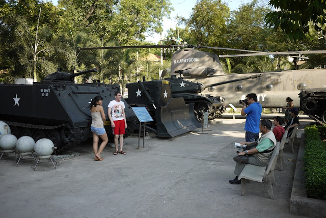 two young people being photographed in front of a U.S. tank