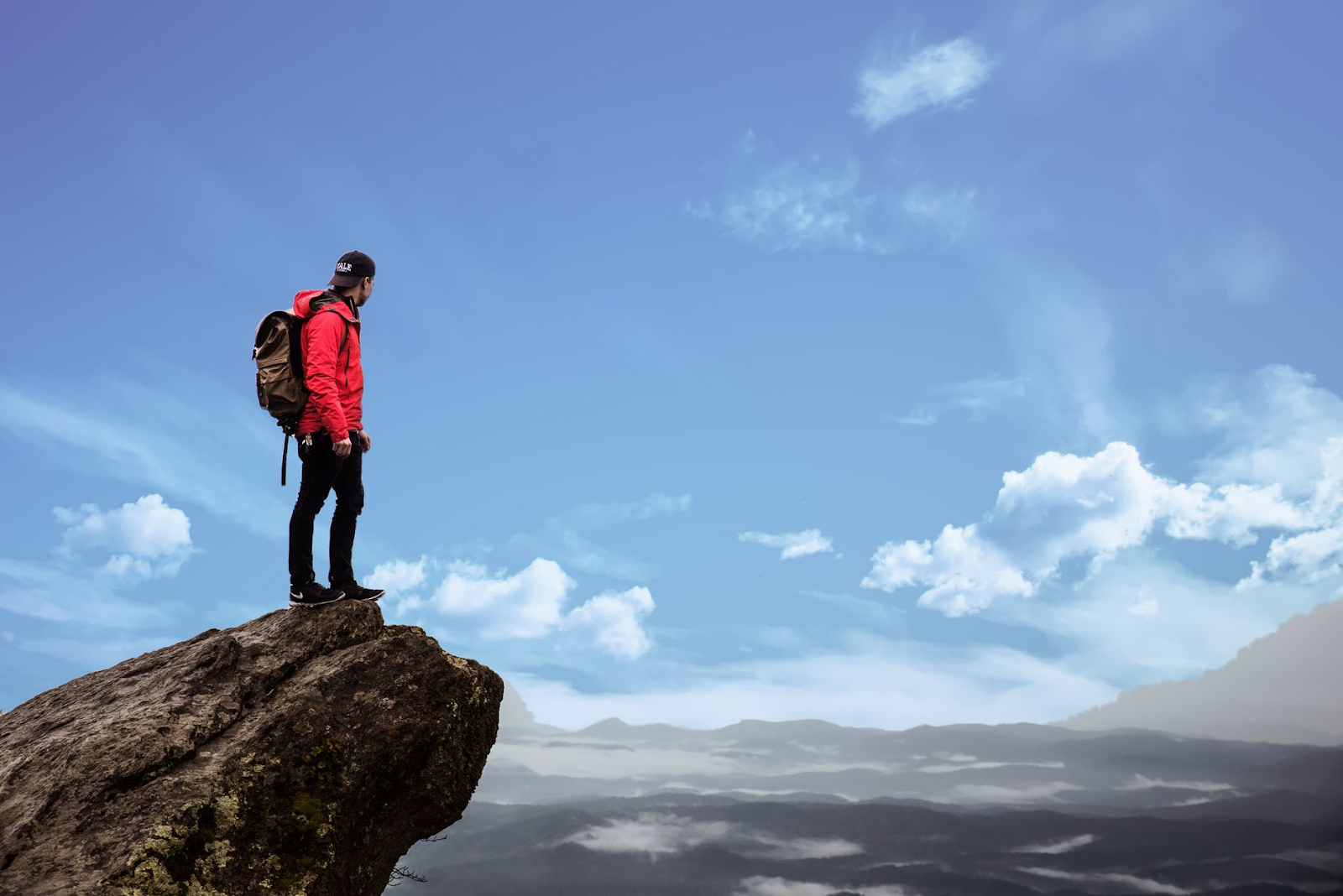 Man stood on the edge of a rock with the sky in the background