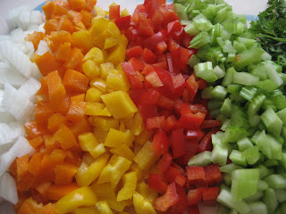 Colorful veggies lined up on a cutting board, from left to right: onions, orange bell peppers, yellow bell peppers, red bell peppers, celery.
