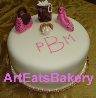 Birthday cake with sugar sculpture shoe, pearl ring, purse and gift bag.