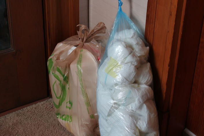 a bag of kitchen trash and a bag of diapers