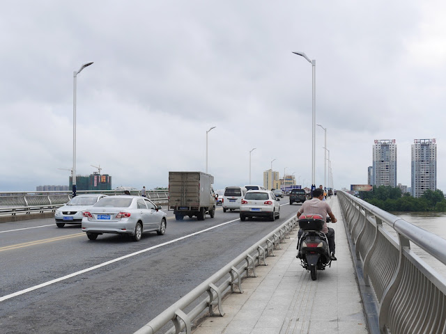 man riding a motorbike on the sidewalk portion of a bridge