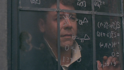 John Nash writing mathematics equations on the window of his dorm room as his dealing with schizophrenia begin to show.