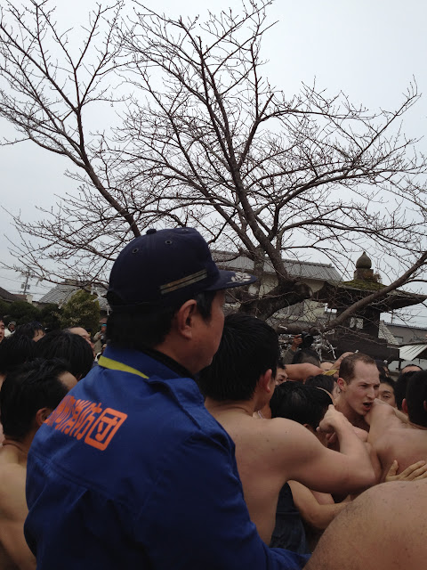 An attendant watches men in loincloths crowding and jostling together