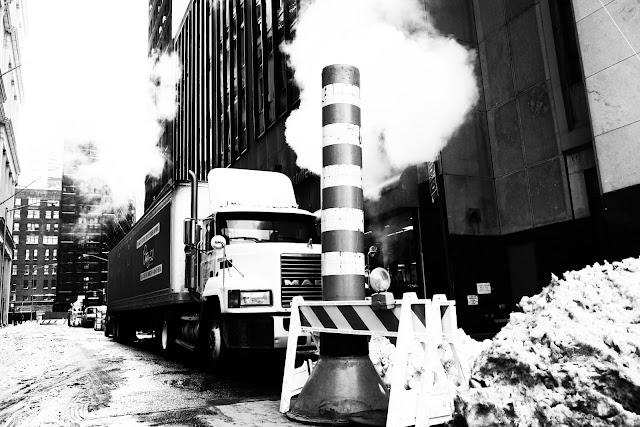 A Mack truck and a steam cloud on a really cold winter day in January near ground zero in New York City.