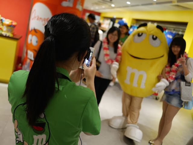 M&M's World staff taking a photo of customers with an M&M's character in Shanghai