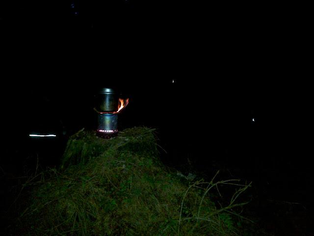 Schon im Dunkeln Abends kocht das Essen im Hobo auf einem Baumstumpf ...