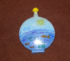 Fill a bottle with blue Sand and paint fishes on top of the bottle- Pretend Aquarium