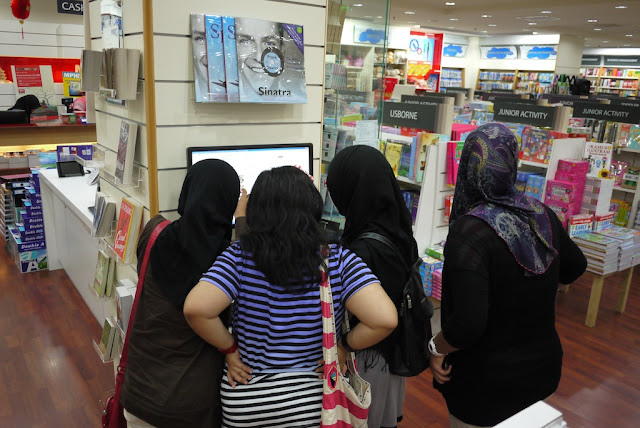 4 girls, 3 wearing a hajib, looking at a computer screen in a bookstore