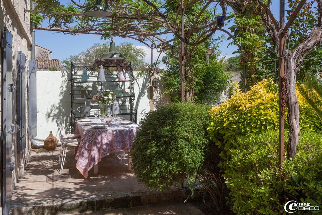 La terrasse d'un mas provençal s'abrite des rigueurs du soleil grâce à une glycine accrochée à une treille