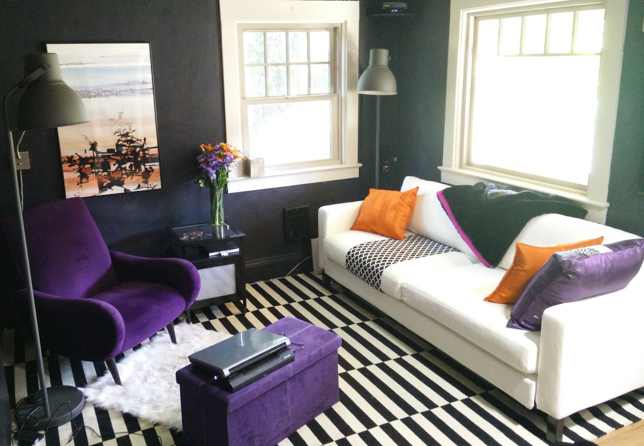 DarkEm's living room showing a white couch, a black and white striped rug, and a purple armchair