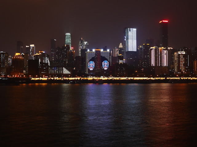 view of Jiefangbei, Chongqing, and some of its surrounding area as seen from across the Yangtze River at night