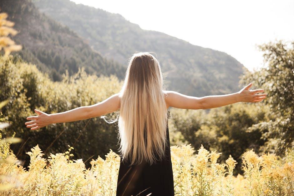 山に直面して黒のドレスで立っている人