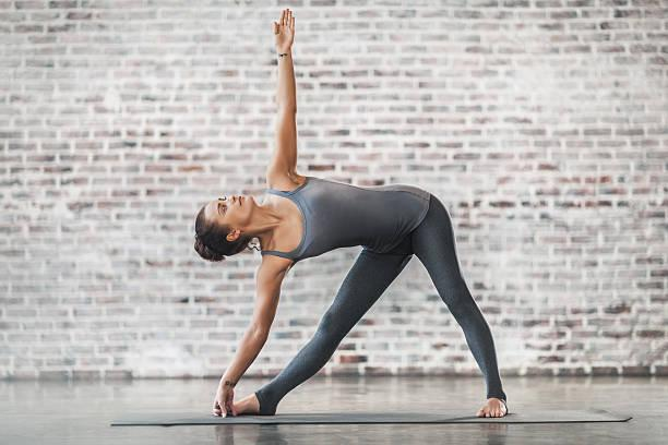 Young Woman Doing Yoga Meditation and Stretching Exercises Young Woman Doing Yoga Meditation and Stretching Exercises. Triangle Pose. Stock photo. extended triangle pose stock pictures, royalty-free photos & images