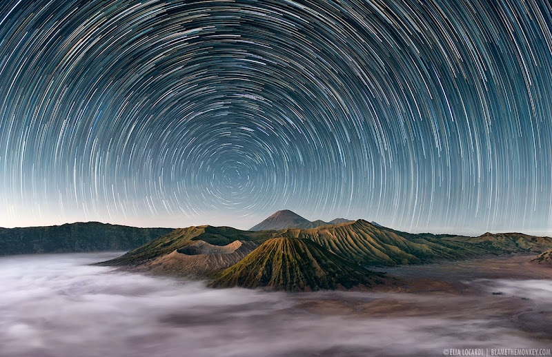 The stars dance above the extraordinary Mt Bromo Indonesia as the morning fog rolls through the caldera. Photographer Elia Locardi