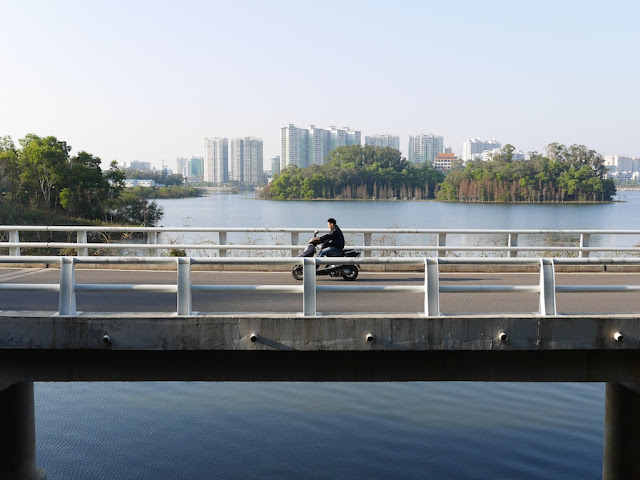 man on motorbike on bridge over Yuanyang Lake in Yangjiang, China