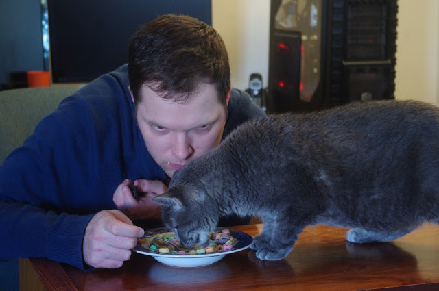 Man and cat eat breakfast