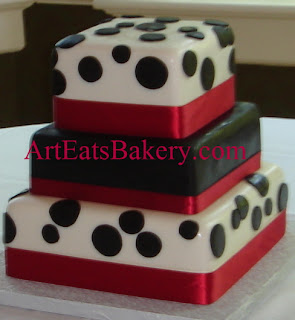 Three tier square custom designed black and white polka dot fondant wedding cake with red ribbons