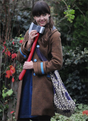 Jessica Alba in a screenshot from the movie *An Invisible Sign* - she has her hair in bunches, is wearing a winter coat and a shoulder bag and is holding an axe while smiling