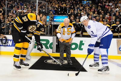 Alumni legend Milt Schmidt of the Boston Bruins does the ceremonial puck drop with Zdeno Chara and Dion Phaneuf