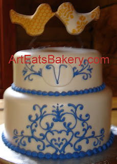 Two tier white fondant wedding cake with custom cornflower blue piping design and monogram and bird topper