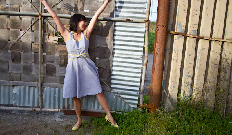Janice wearing a grey seersucker dress in front of a shipping container