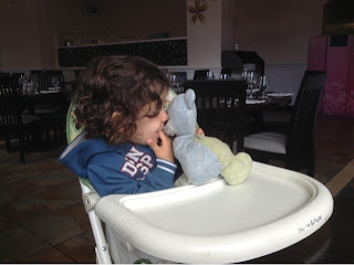 toddler in highchair with teddy bear