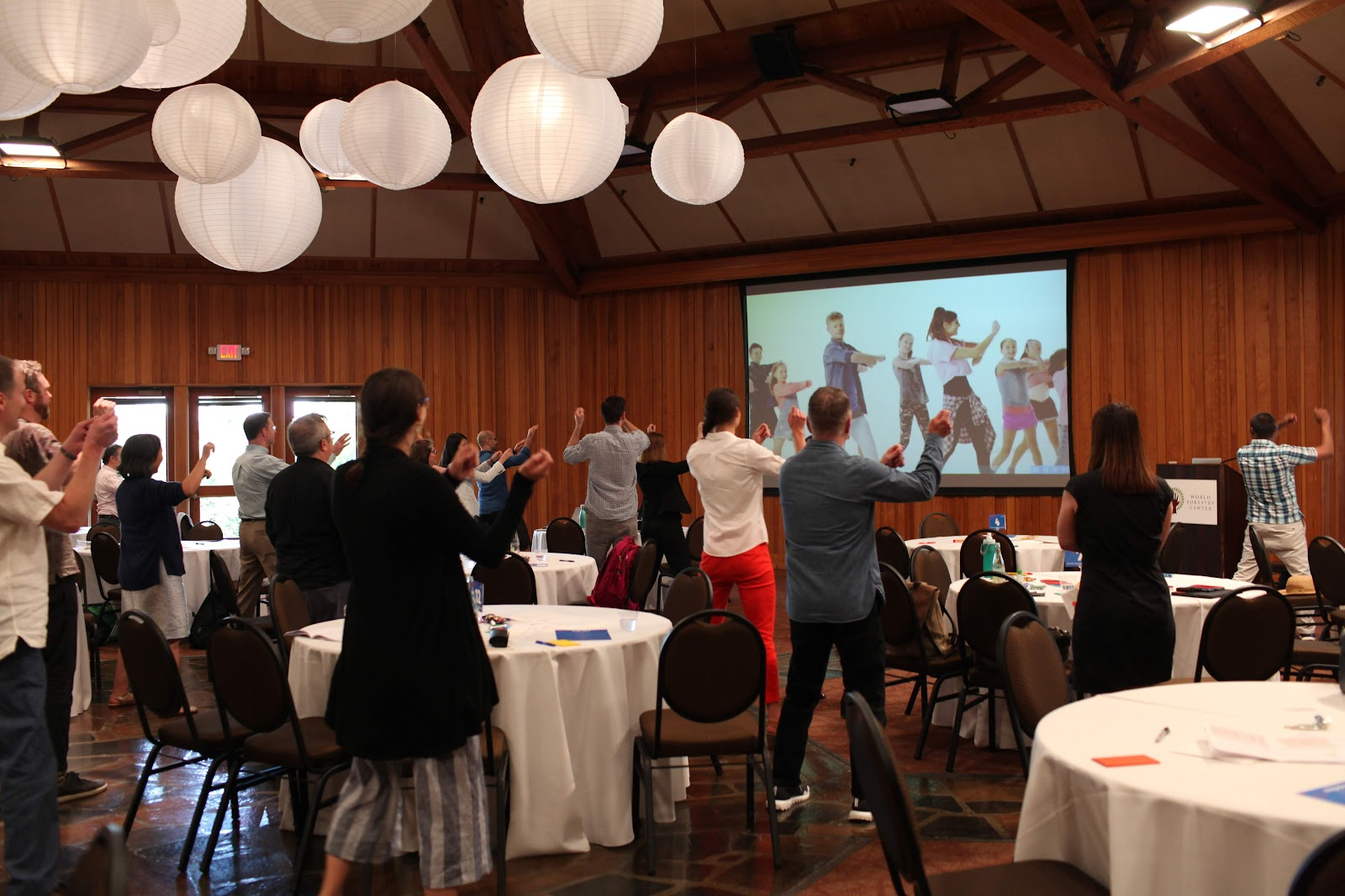 ILN participants dancing to disco music in the middle of the conference as a mid-day exercise.