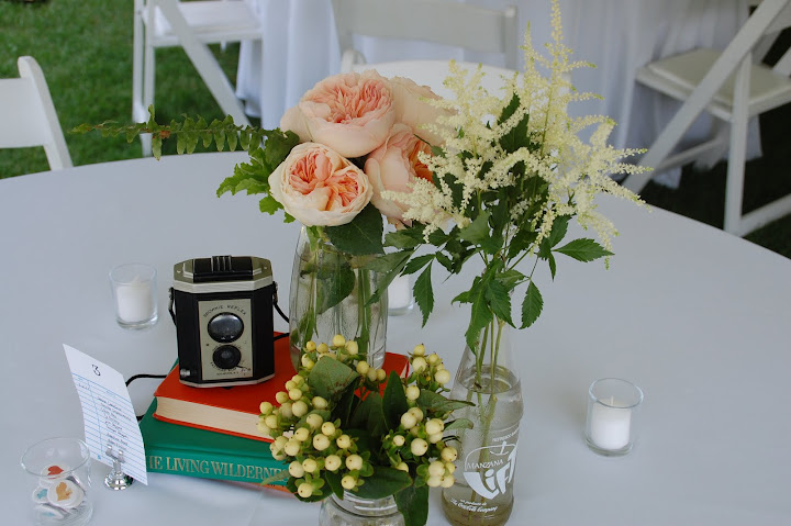 Vintage camera and bottles of flowers as wedding centerpieces