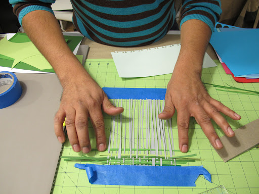 Careful weaving of paper strips.