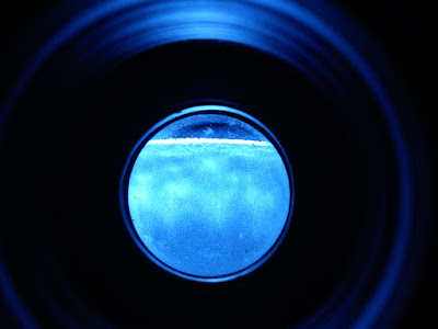 View through 40mm eyepiece used as Loupe, of mirror's edge.  Visible roughness on what remains of the bezelled edge, but surface totally pit-free, ready to move on from #400 grit.