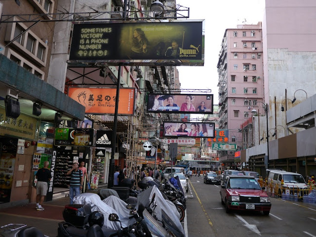 advertisements hanging over a sidewalk and street in Mongkok, Hong Kong