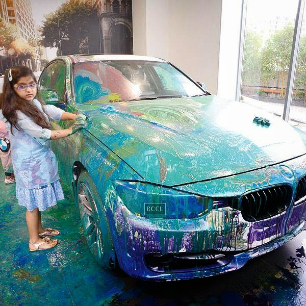 A girl paints the car during an event organised by BMW Parsoli Motors and Little Big Joys.