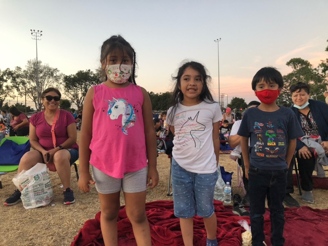 Three children at a Movies in the Park event at Rosita Park. Their mother smiles in the background sitting down. The kids are standing on a red blanket, they are young, probably between 6-8 years old.