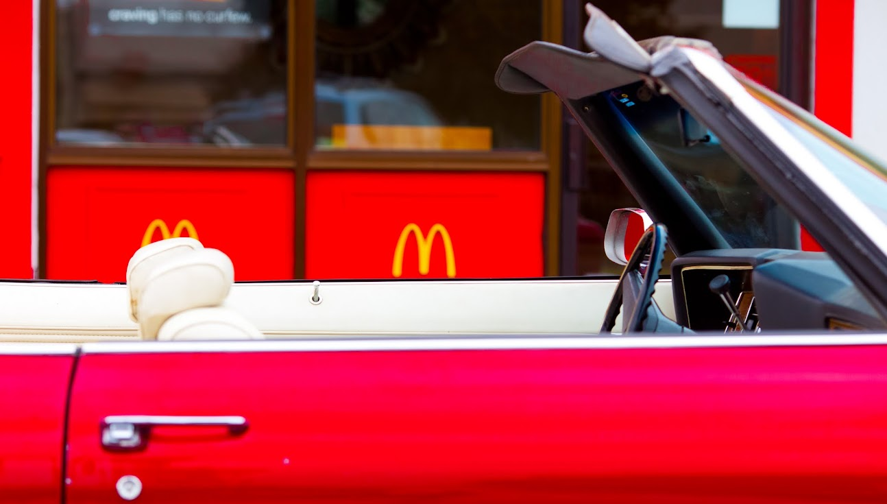 A red convertable at a McDonald's drive-thru