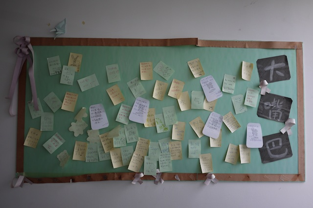 bulletin board with notes in a college dormitory room in Changsha, China
