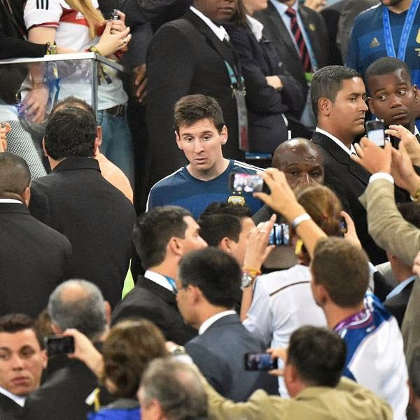 Spectators take photos of Argentina's Lionel Messi as he walks down after getting his runners-up medal after the World Cup final soccer match between Germany and Argentina at the Maracana Stadium in Rio de Janeiro, Brazil, Sunday, July 13, 2014. Germany won the match 1-0.