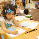 Our older preschool students start learning about some advanced topics. This girl is copying notes from a lesson about the sun and earth, writing down why we have night and day on earth.