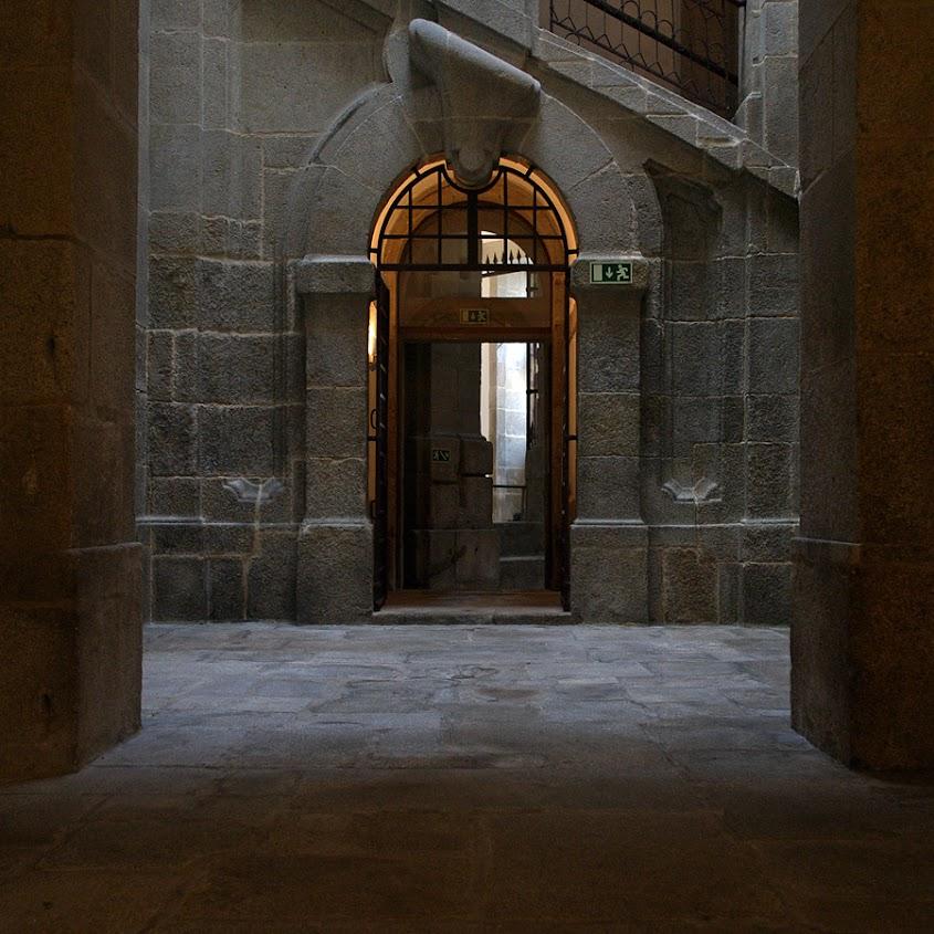 Páteo interior em granito  e uma porta. Tudo iluminado pela luz de uma clarabóia, não visível na imagem