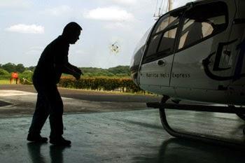 ヘリコプターの脇でヘリコプターのおもちゃを飛ばす